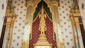 La estatua de oro del ángel y la arquitectura tailandesa del arte detallan el pasillo principal de la ordenación en el templo bud Foto de archivo
