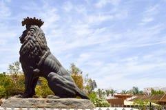 la estatua de piedra hermosa grande de un león majestuoso orgulloso negro en un pedestal contra un cielo azul y copia el lugar fotos de archivo