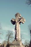 La estatua de piedra vieja de Jesús crucificó en la cruz en el tombston Imagen de archivo libre de regalías