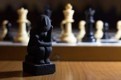 la estatua del pensador en pensamiento de la bobina del tablero de ajedrez un pequeño en el st Foto de archivo