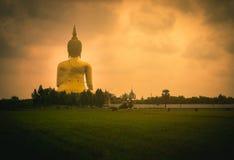 La estatua más grande de Buda en la puesta del sol en templo Foto de archivo libre de regalías