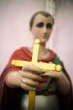 La estatua religiosa que lleva a cabo la cruz del oro en una iglesia altera Foto de archivo libre de regalías