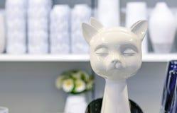 La estatuilla de cerámica blanca de un gato con los ojos se cerró imagen de archivo