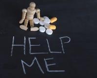 La estatuilla humana de madera con las píldoras y me ayuda en la pizarra Fotografía de archivo libre de regalías