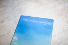 La estera azul de la yoga miente en el piso Foto de archivo libre de regalías