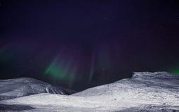 La estrella ártica polar del cielo del aurora borealis de la aurora boreal en Noruega Svalbard en montañas de la luna de la ciuda Imagen de archivo