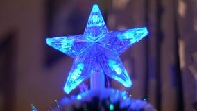 La estrella de la Navidad brilla intensamente con lighChristmas coloreados que el árbol en sitio brilla con las luces azules, roj almacen de video
