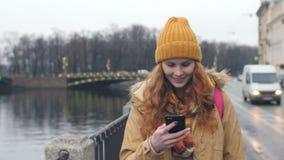 La estudiante camina en la ciudad del otoño y escribe SMS al teléfono metrajes