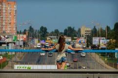 La estudiante elegante hermosa se coloca en el puente del coche con un b Fotografía de archivo