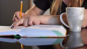 La estudiante escribe en primer del cuaderno en casa almacen de metraje de vídeo