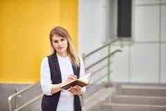 La estudiante se coloca en los pasos del edificio y de los sue?os imagen de archivo