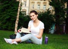 La estudiante sonriente en ciudad parquea con el libro Fotografía de archivo