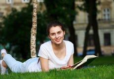 La estudiante sonriente en ciudad parquea con el libro Imagenes de archivo