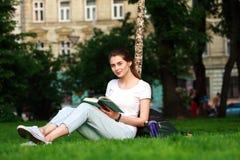 La estudiante sonriente en ciudad parquea con el libro Fotos de archivo libres de regalías