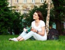 La estudiante sonriente en ciudad parquea con el libro Foto de archivo libre de regalías