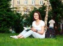 La estudiante sonriente en ciudad parquea con el libro Fotos de archivo