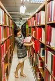 La estudiante universitaria tailandesa está seleccionando el libro del estante Imagen de archivo libre de regalías