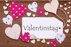 La etiqueta, corazones rosados, texto Valentinstag significa día de tarjetas del día de San Valentín Fotografía de archivo
