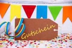 La etiqueta del partido con la flámula, texto Gutschein significa el vale Imagen de archivo libre de regalías
