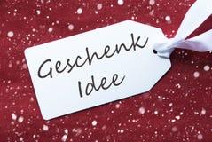 La etiqueta en el fondo rojo, copos de nieve, Geschenk Idee significa idea del regalo Fotografía de archivo