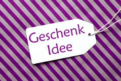 La etiqueta en el papel de embalaje púrpura, Geschenk Idee significa idea del regalo Foto de archivo