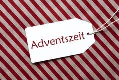 La etiqueta en el papel de embalaje rojo, Adventszeit significa a Advent Season Fotos de archivo