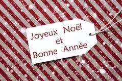 La etiqueta en el papel rojo, copos de nieve, Bonne Annee significa Año Nuevo Fotos de archivo libres de regalías
