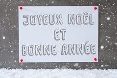 La etiqueta en la pared del cemento, copos de nieve, Bonne Annee significa Año Nuevo Fotografía de archivo
