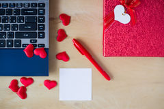 La etiqueta engomada vacía, PC, pluma, caja adornó corazones en la tabla de madera Imágenes de archivo libres de regalías