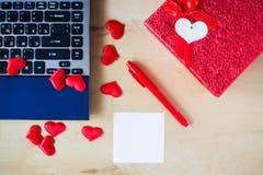 La etiqueta engomada vacía, PC, pluma, caja adornó corazones en la tabla de madera Imagenes de archivo