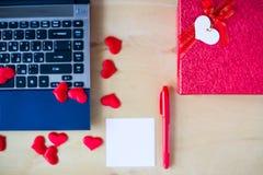 La etiqueta engomada vacía, PC, pluma, caja adornó corazones en la tabla de madera Fotos de archivo