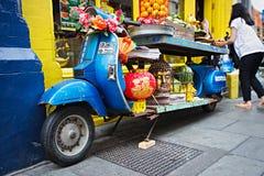 La exhibición azul de la moto con las frutas, verduras, sátiras virulentas, cabeza de Buda delante del chino hace compras, festiv Fotografía de archivo libre de regalías