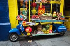 La exhibición azul de la moto con las frutas, verduras, sátiras virulentas, cabeza de Buda delante del chino hace compras, festiv Fotos de archivo libres de regalías
