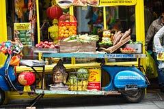 La exhibición azul de la moto con las frutas, verduras, sátiras virulentas, cabeza de Buda delante del chino hace compras, festiv Imagen de archivo
