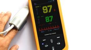 La exhibición del oxímetro del pulso que muestra el oxígeno noventa y siete de la sangre en amarillo y pulsa ochenta y siete en v imágenes de archivo libres de regalías