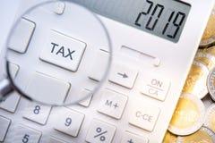 La exhibición número 2019 de la calculadora y la lupa enfocan adentro botón del impuesto foto de archivo libre de regalías