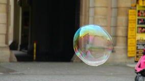 La explosión colorida de las burbujas de jabón en ciudad, burbuja enorme salpica metrajes