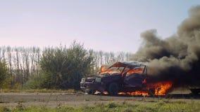 La explosión de la rueda de un coche que quema en la carretera Coche en el fuego en el camino metrajes