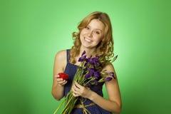 La explotación agrícola atractiva de la muchacha florece y un rectángulo de regalo Fotos de archivo libres de regalías