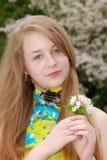 La explotación agrícola femenina joven del adolescente florece en un jardín Fotografía de archivo libre de regalías