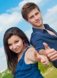 La explotación agrícola joven feliz de los pares manosea el cielo con los dedos ascendente y azul Foto de archivo