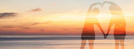La exposición doble de pares hace una forma del corazón con su cuerpo sobre el mar en el tiempo crepuscular del cielo Imágenes de archivo libres de regalías