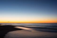 La exposición larga como el sol sube a través del Océano Atlántico Imagen de archivo libre de regalías