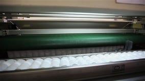 La fábrica para hacer los colchones, máquina transporta un bloque de primaveras independientes llenas en una envoltura, transport almacen de metraje de vídeo