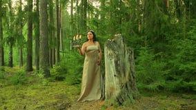 La fée mystérieuse de forêt se tient prêt un grand tronçon avec des bougies et tient un chandelier avec les bougies brûlantes ded banque de vidéos