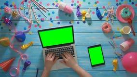 La fête d'anniversaire de planification d'homme de vue supérieure utilisant l'ordinateur portable et le comprimé numérique verdis banque de vidéos