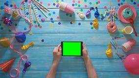 La fête d'anniversaire de planification d'homme de vue supérieure utilisant le comprimé numérique fait des gestes avec l'écran ve banque de vidéos