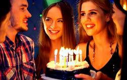 La fête d'anniversaire heureuse d'amis avec la célébration de bougie durcit dans le club Photos stock