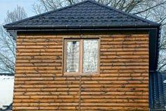 La façade d'une maison en bois faite de rondins avec une fenêtre brune Images stock