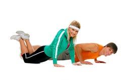 La fabbricazione adatta dell'atleta del maschio e della ragazza spinge verso l'alto l'attrezzo ginnico Fotografia Stock